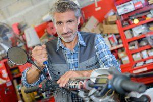 man repairing motorbike in a storag unit