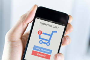 Hand holding phone showing online shopping cart