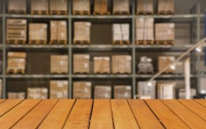 Abstract blurred boxes on rows of shelves in big modern warehous