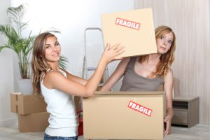 girls with packing boxes moving house