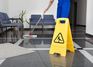 cleaner mopping floor with safety sign